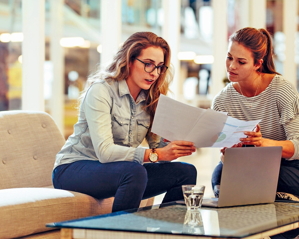 Two women sitting discussing over paperwork