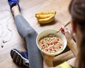 Woman in fitness attire eating oatmeal with berries